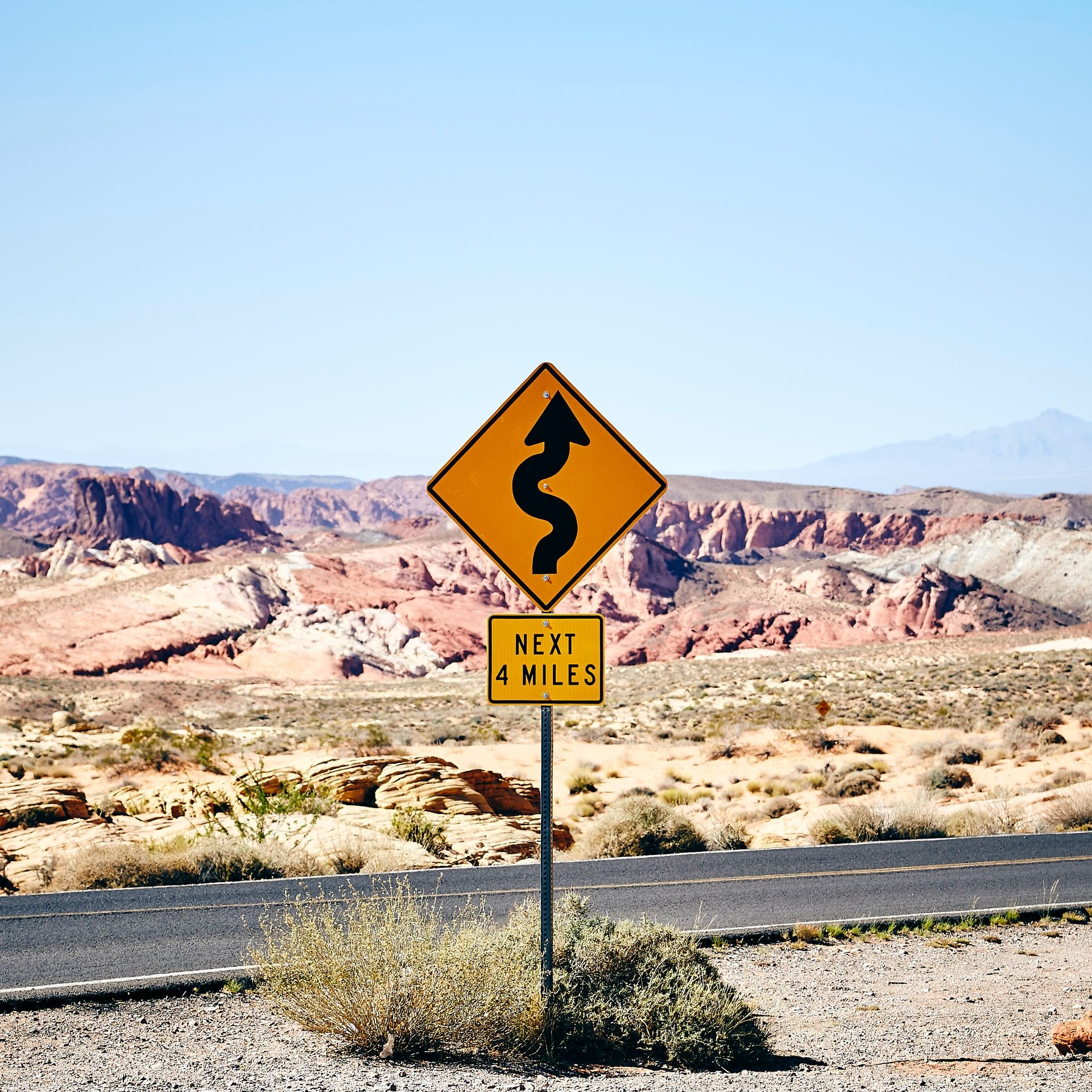 Sign on desert road that shows curves for the next four miles