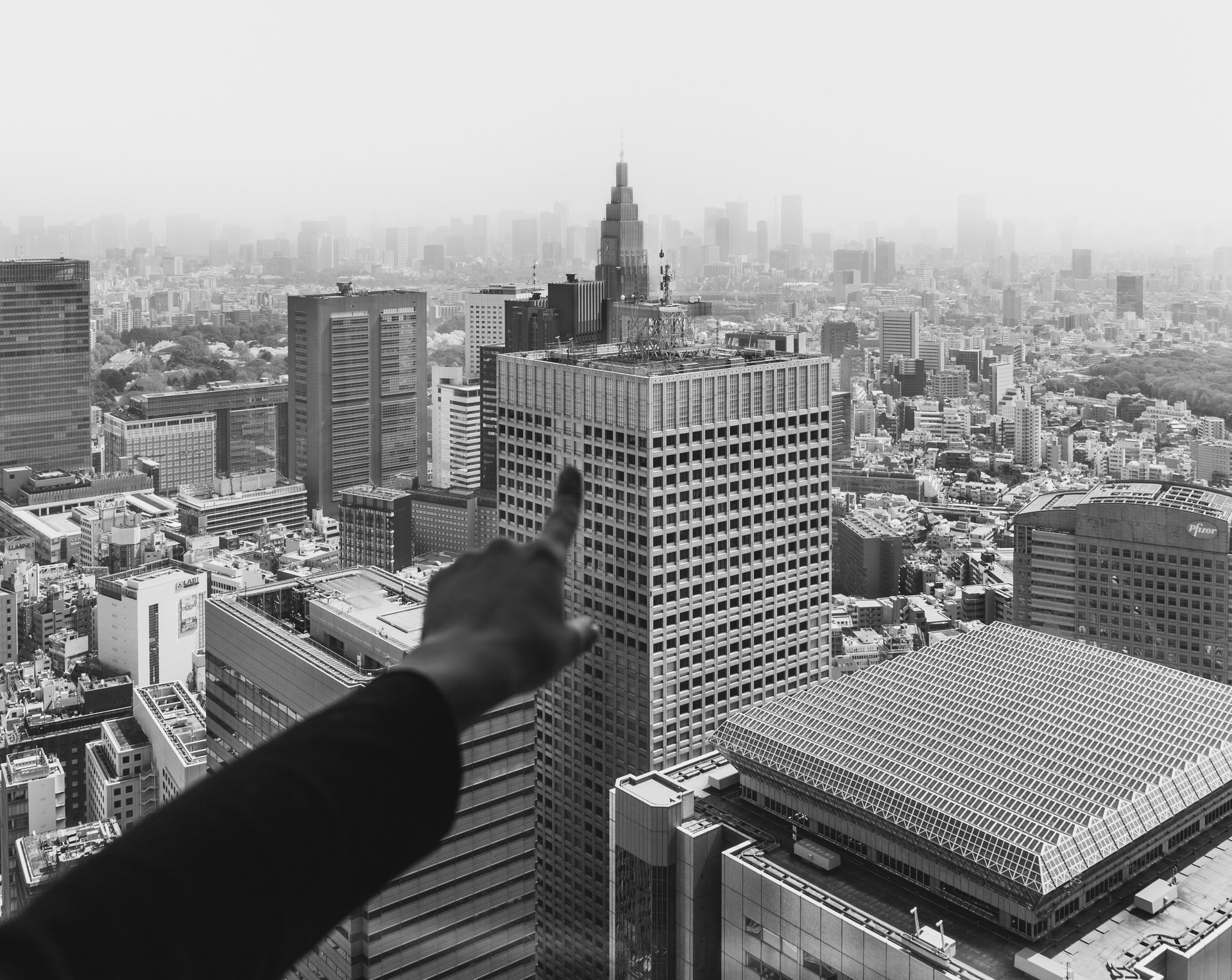 Finger pointing at a skyscraper in a large city