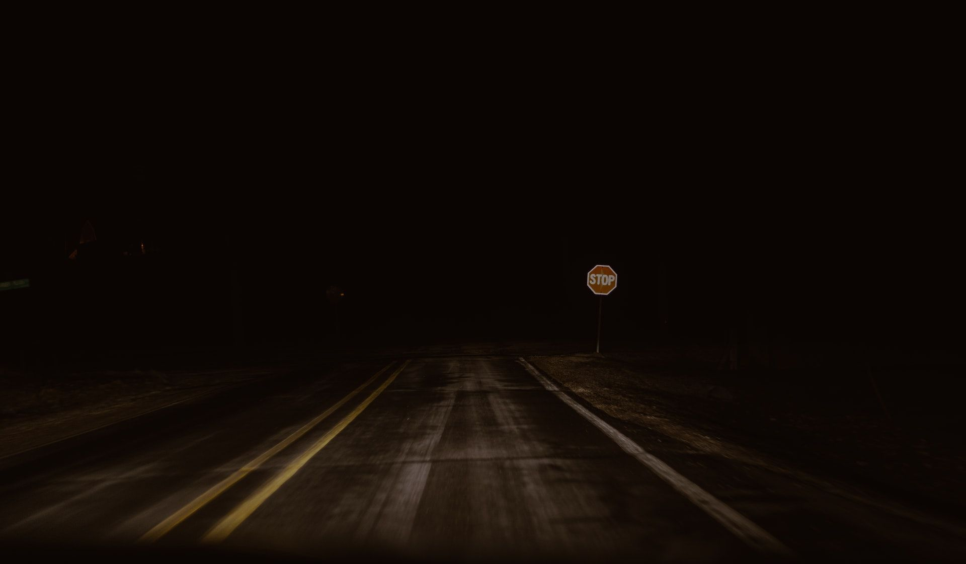 Road in the dark with poor lighting, a stop sign just visible in the distance