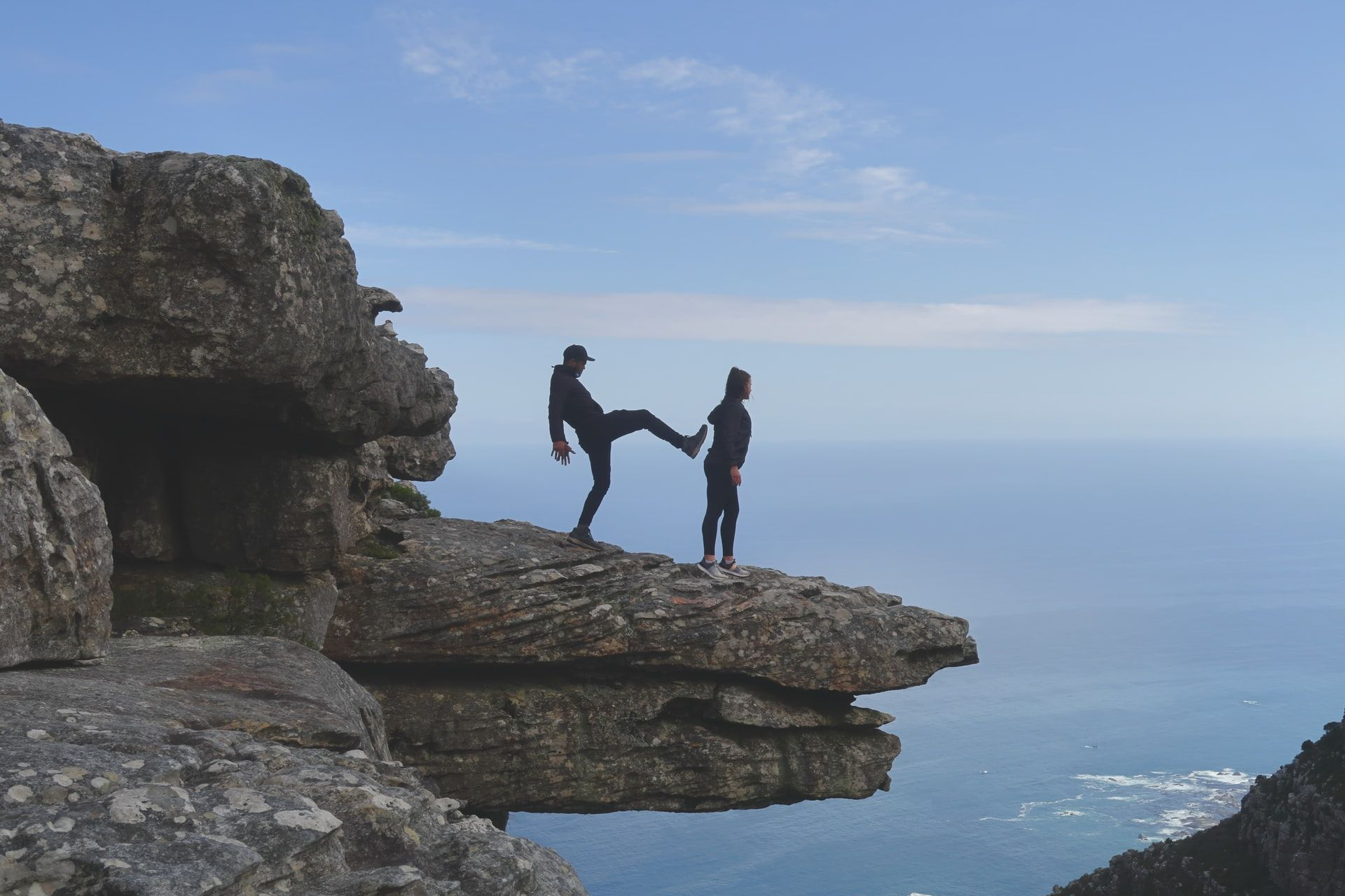 Table Mountain (Nature Reserve), Cape Town, South Africa . On a table of rock overlooking a valley, a man faces a woman with one leg up as if he is about to kick her off. She faces the valley.