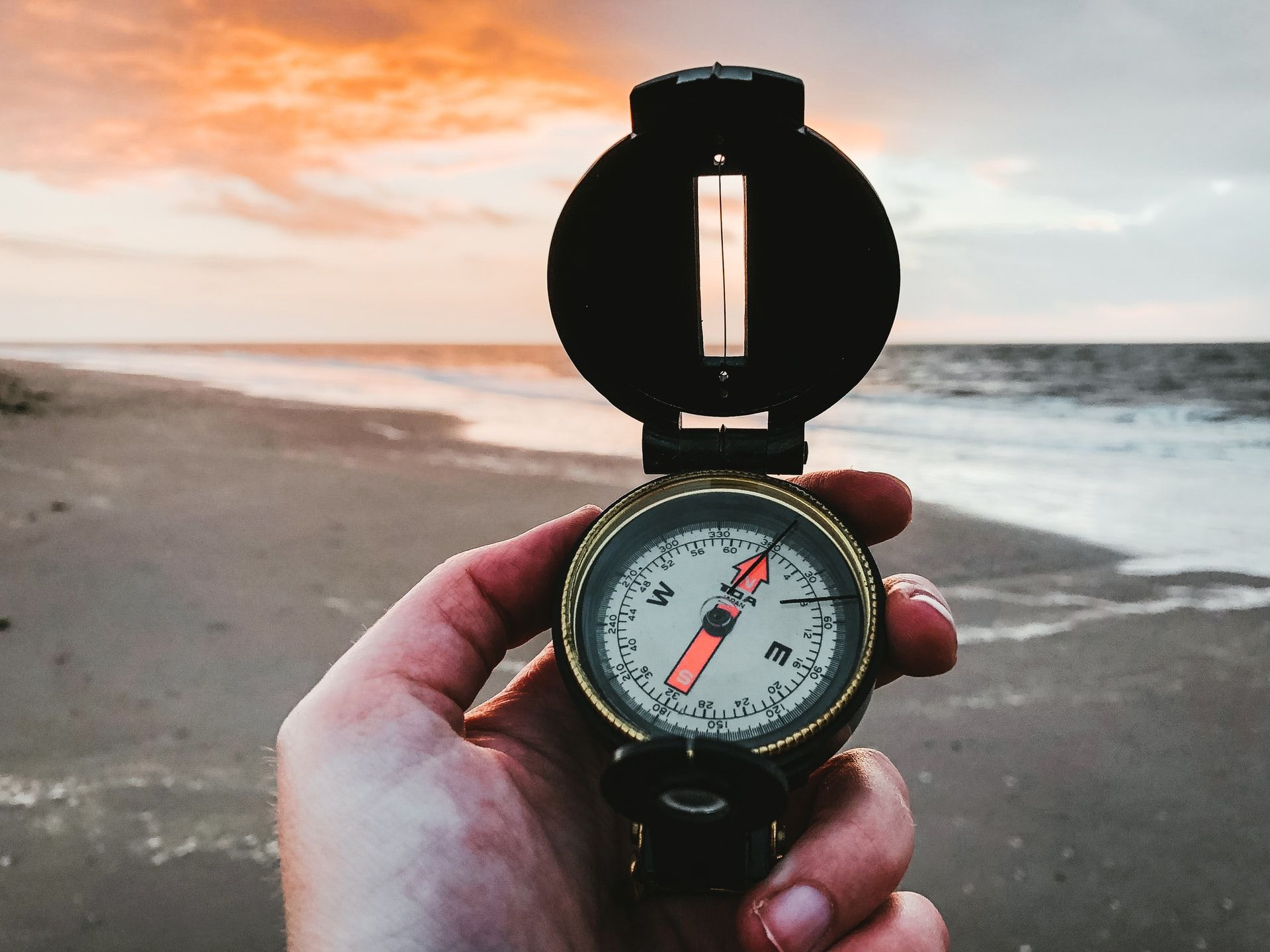 Person holding a compass at the beach