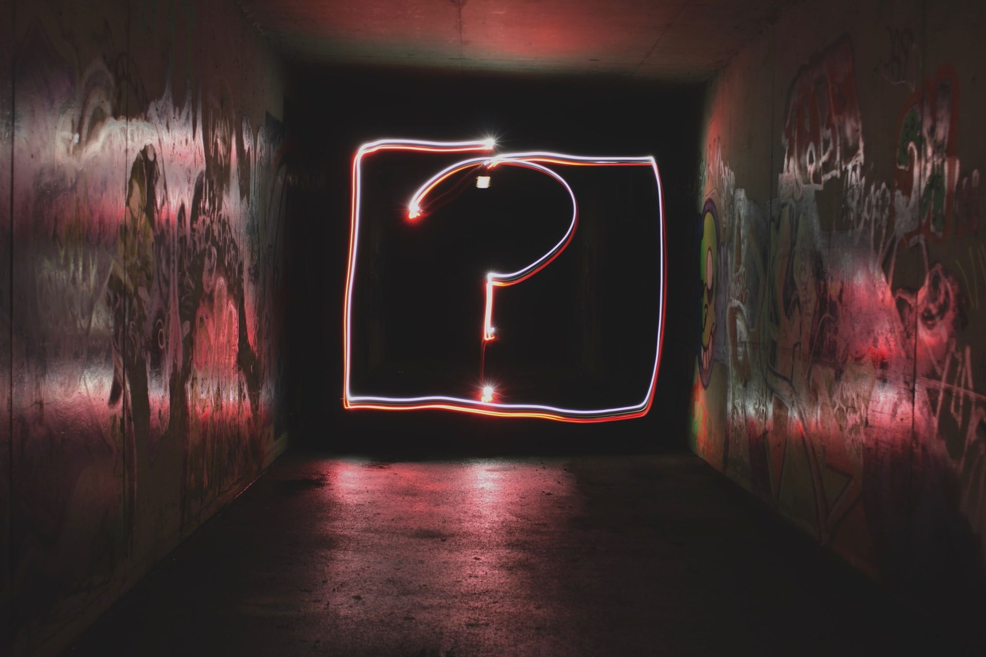 Looking down a dark tunnel at night. At the end of a tunnel is a person waving a glow stick in the form of a question mark.