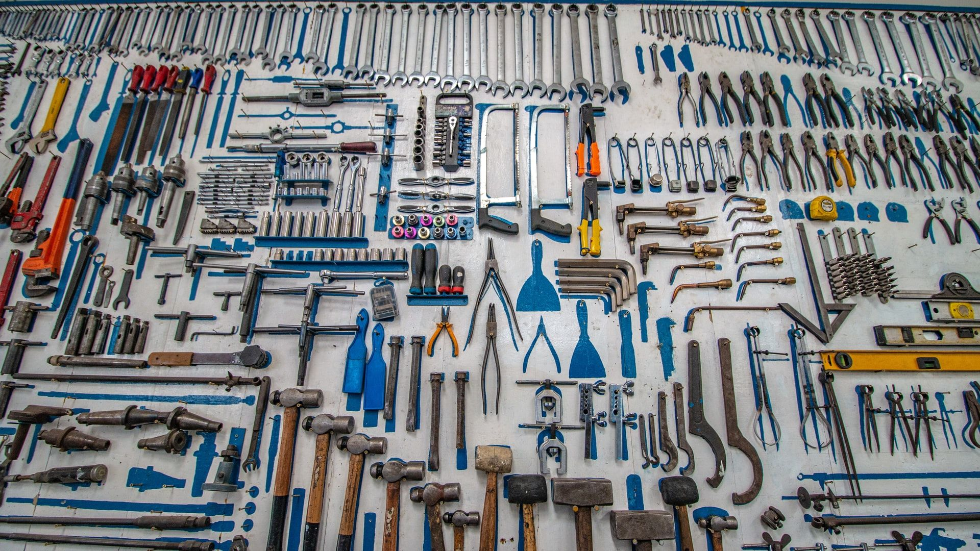 A large number of tools hanging on pegs in a wall. The tools are all hand tools and very near to one another.