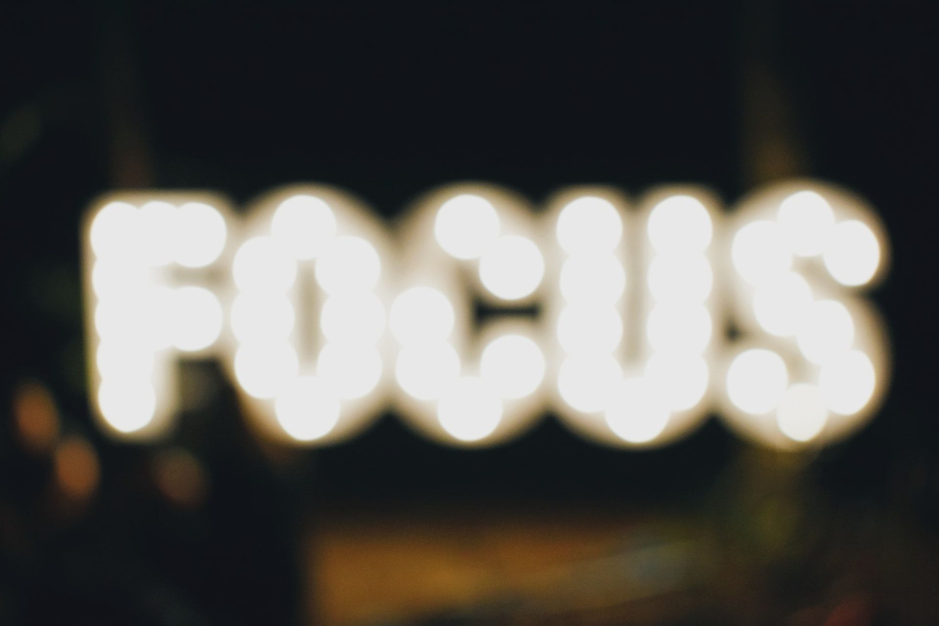 A neon sign that says 'focus' that is out of focus